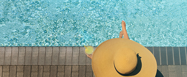 Guest in large hat enjoying a drink poolside